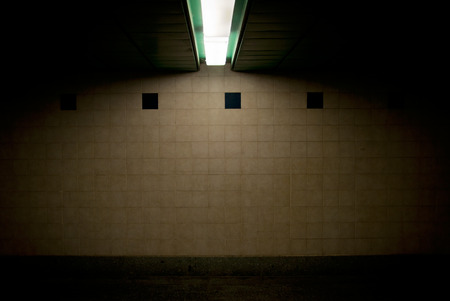 horror background: lit tiled wall in the subway - horror background