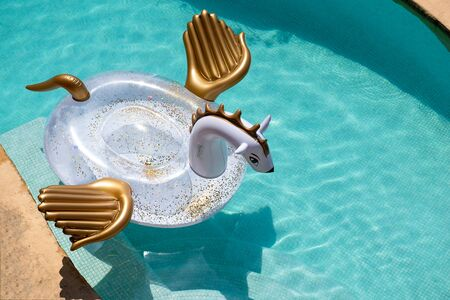 Giant inflatable Pegasus in the pool with clear azur water Standard-Bild