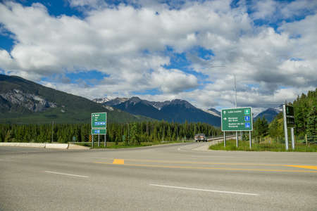 Mountain Highway road with car. Crossroad and sign. Summer time. Banff, Alberta, Canada