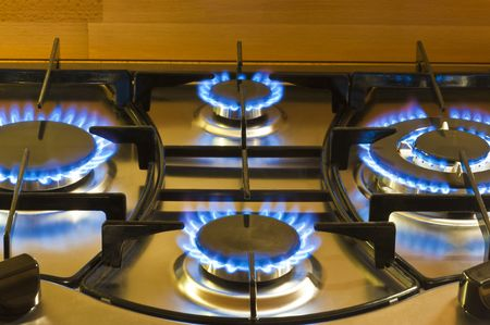 burner: closeup of a cooker hob with the gas lit
