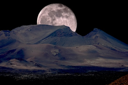inactive:  Full moon rising over an inactive volcano.  Stock Photo