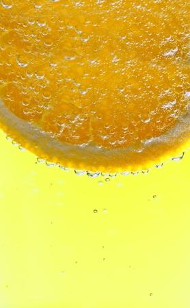 freshly sliced orange in soda pop with a lemon orange  background photo