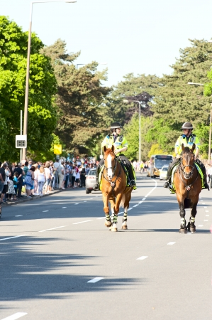 bearer: CARDIFF,WALESUK-MAY 25, 2012;The Police on horse-back escorts, the bearer of the torch relay team bringing the torch into Cardiff on its tour of the UK Editorial