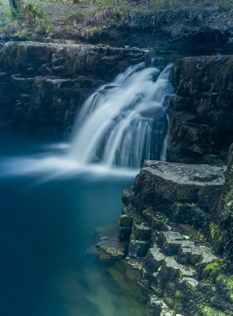 A waterfall is a place where water flows over a vertical drop in the course of a stream or river photo