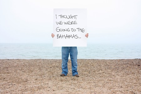 A man holding a sign on a winters beach in the uk