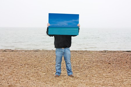 mersea: A man standing on a beach with a picture of a tropical beach