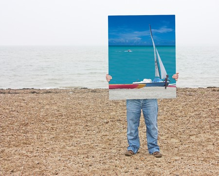 mersea: A man standing on a beach with a photo of a tropical beach