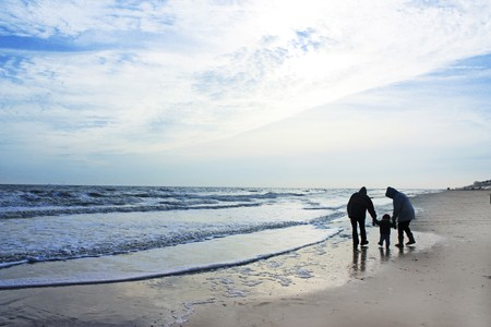 A strong silhouette of grandparents and child on a winter beach photo