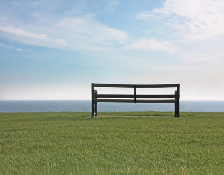 An empty bench looking out to sea photo