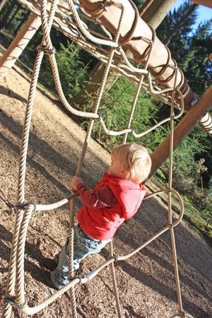Photo of a two year old boy in a play park in a forest photo