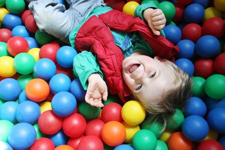 Two year old boy in a pool of coloured balls photo