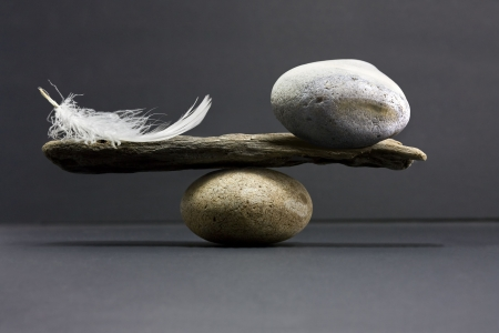 and harmony: a feather and a stone equally balance