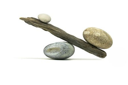 unbalanced: heavy stone on tower of driftwood and beach stones
