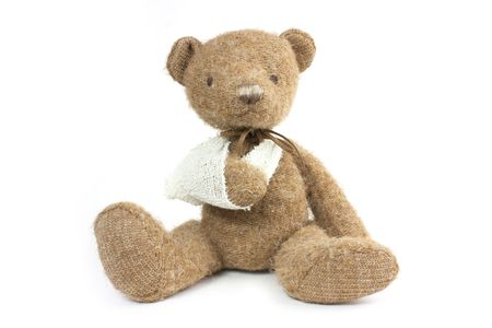 head toy: cute teddy bear with a broken arm in a sling Stock Photo