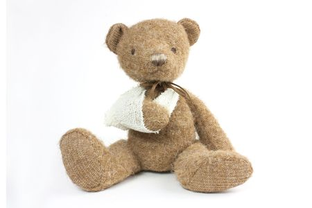 cute teddy bear with a broken arm in a sling photo