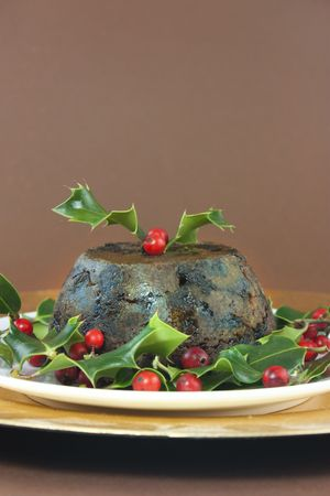 christmas pudding: christmas pudding with holly and red berries on brown background Stock Photo