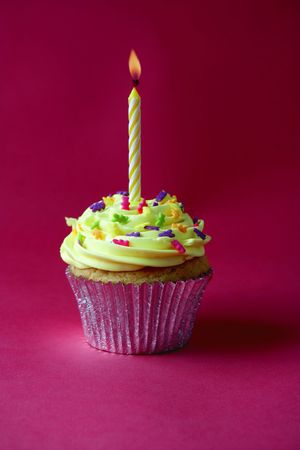 first birthday: cupcake with a single candle on a red background