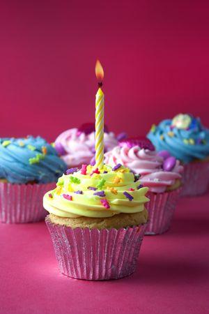 torta compleanno: gruppo Cupcake girato su uno sfondo rosso  Archivio Fotografico