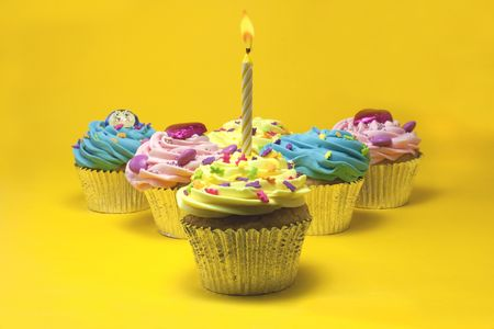 cupcakes shot on a yellow background with one candle photo