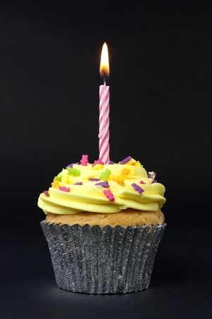 cupcake shot on a black background with one candle photo