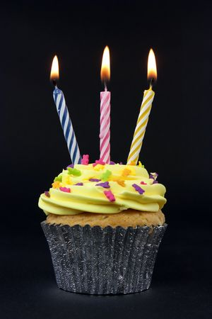 happy birthday candles: cupcake on black with 3 candles on black Stock Photo