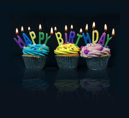 happy birthday cake: cupcakes deletrear cumplea�os feliz sobre un fondo negro con la reflexi�n Foto de archivo