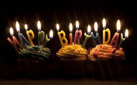 auguri di buon compleanno: Cupcake girato su uno sfondo nero con candele di buon compleanno