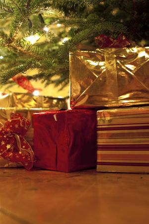 Wrapped islver, red and gold gifts under the christmas tree photo