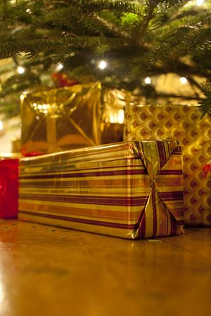 Presents under a real christmas tree, gold, silver and red photo