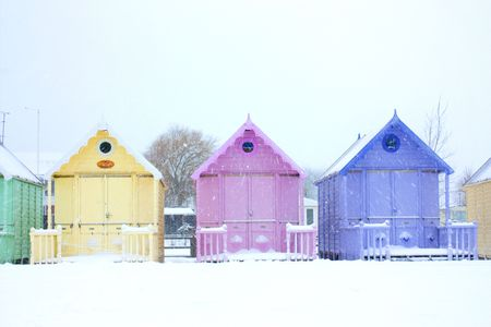 mersea: beach huts close up in a snowstorm in west mersea, essex