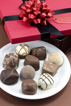 box of chocolates wrapped in a red ribbon as a gift photo