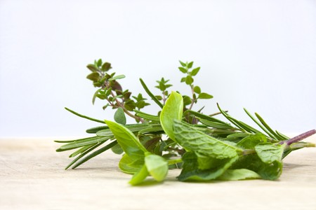 sage: fresh herbs shot on a wooden chopping board in the studio