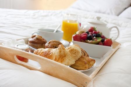 Desayuno en la cama con frutas y pasteles en una bandeja