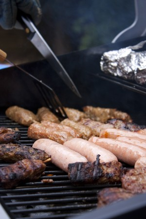 grill tongs sausage: summer bbq in a garden with sausages and burgers