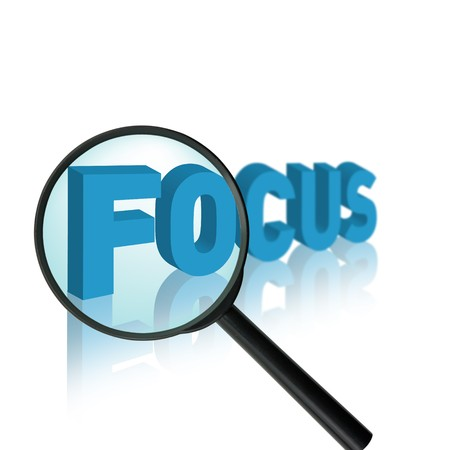 analogy: the word focus with a magnifying glass Stock Photo