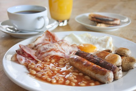 bacon baked beans: cooked breakfast on a wooden table with coffee and orange juice Stock Photo