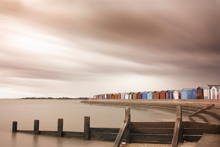 british weather: Shot at brightlingsea beachfront and huts in essex, uk. Long manual exposure to blur sea and clouds. Stock Photo