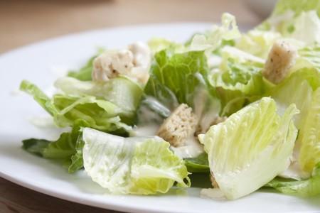 ensalada cesar: Ensalada César se sentó en una mesa de la cocina en el interior con luz natural