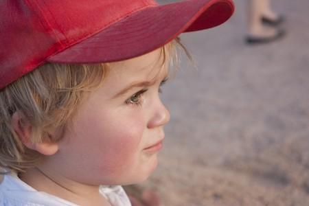 cute blonde boy, toddler wearing red baseball cap in summer photo
