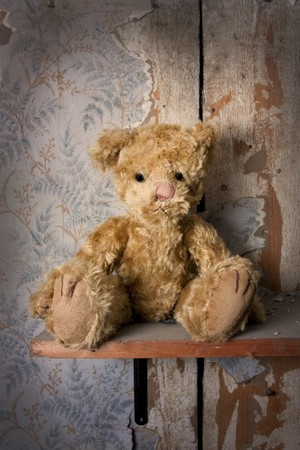 dirty room: Bear alone on a shelf in a old tattered room
