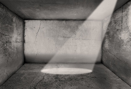 cella carcere: Single potlight brilla in quello che potrebbe essere una cella di prigione o in generale un vecchio grunge testurizzati camera e pareti.