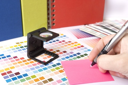 printing proof: graphic design and coloured swatches and pens on a desk