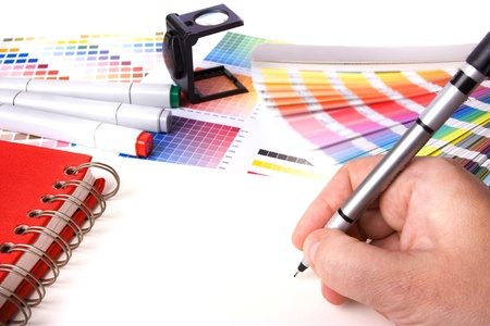 tervező: graphic design and coloured swatches and pens on a desk