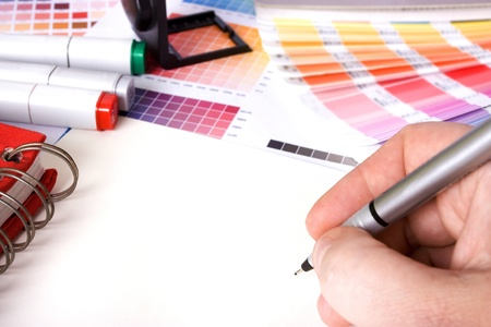 designer: designer surrounded by design colour swatches and pens with blank paper