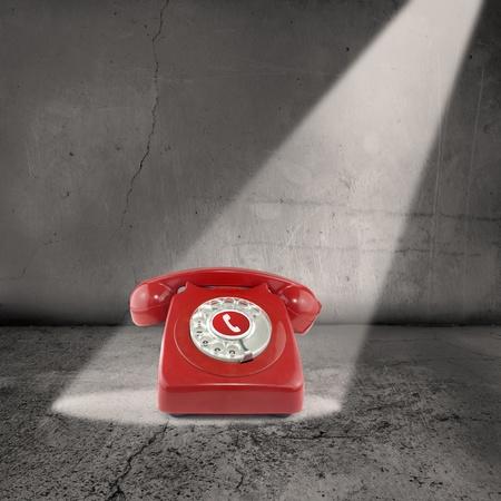 telefono antico: Un unico telefono rosso si siede sotto un beem di luce in una stanza vuota