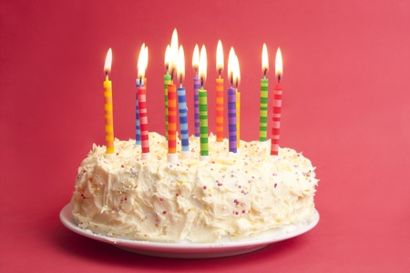 pastel aniversario: pastel de cumpleaños con una gran cantidad de las velas sobre fondo rojo