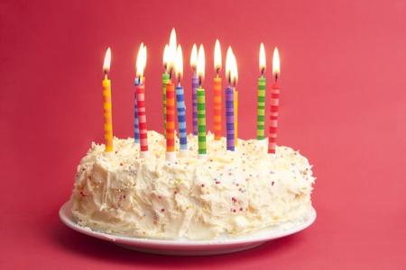 candeline compleanno: torta di compleanno con un sacco di candele su uno sfondo rosso