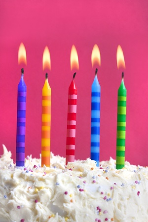 happy birthday candles: Close up macro photograph of 5 candles on a birthday cake