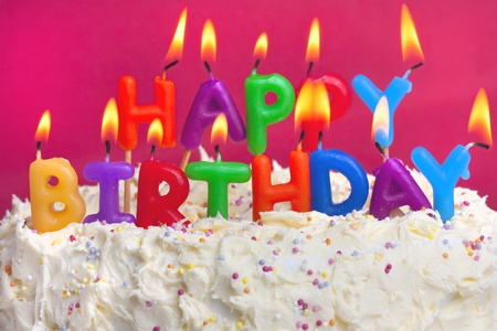 happy birthday cake: colourful lit candles spellign out happy birthday on a cake