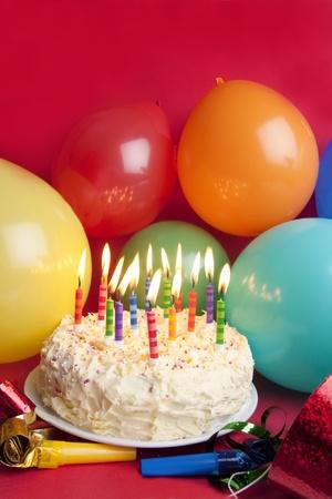 torta candeline: Colpo di studio di compleanno tipico istituito di torta, cappelli e partito palloncini